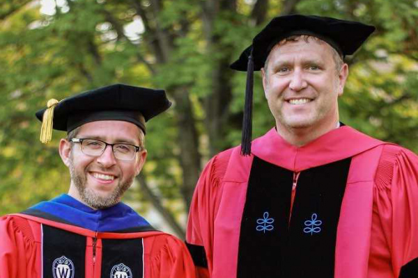 Jeremy Hutton and Preston Atwood pose in graduation robes